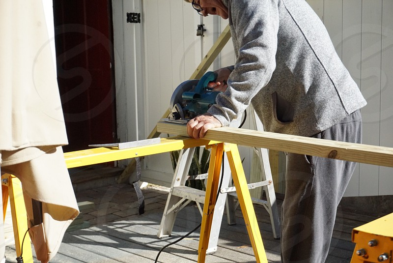 Man active senior working home improvement woodworking sawing wood tools power tools deck creating Carpenter handyman outdoors  photo