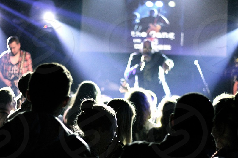 man singing on stage in front of people photo