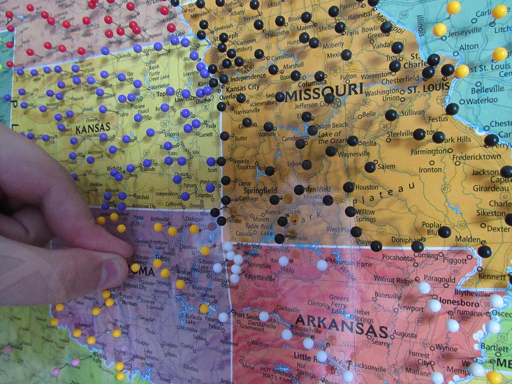 Hand putting pins on a map of locations he's been. photo