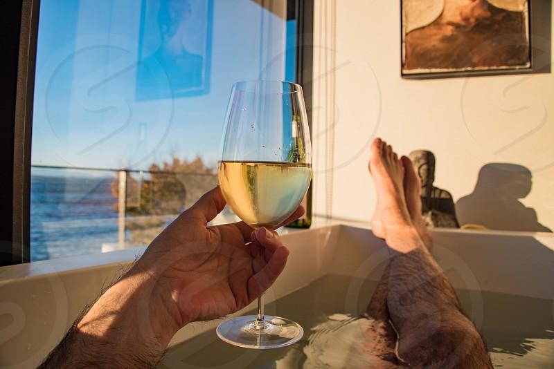 White wine in the tub. man legs wine art wealthy pov. photo