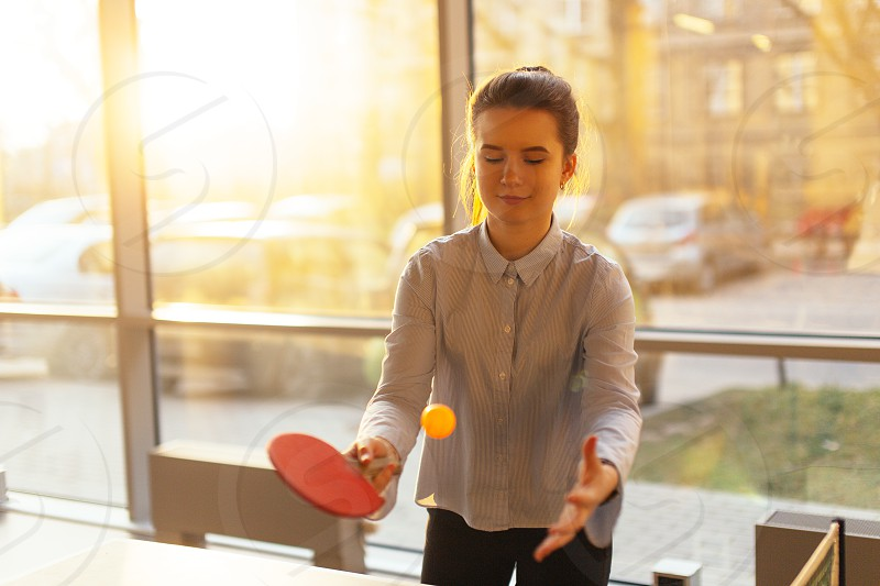 Office place with girl play pin-pong. Smiling girl look at camera and around with pretty face. Office worker break game. photo
