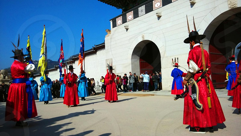 group of people wearing red and blue traditional dresses photo