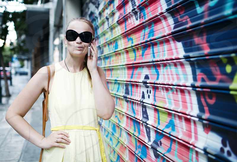 Woman in sunglasses chatting on a mobile phone while standing alongside a wall covered in colourful graffiti or a mural photo