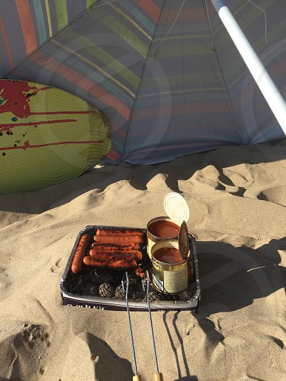Hot dogs on the beach with umbrella and boogie board for wind block photo