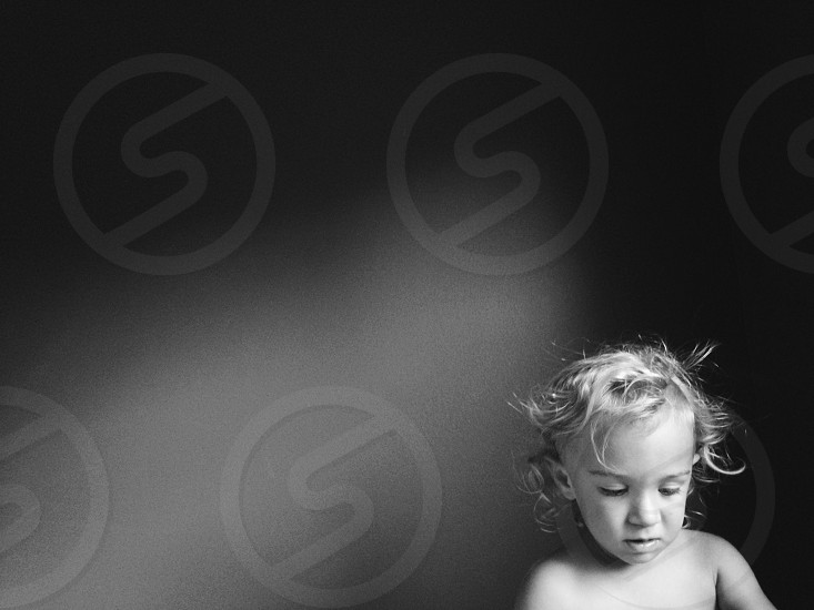 Black and white portrait of toddler with curly hair against shadowed background. photo