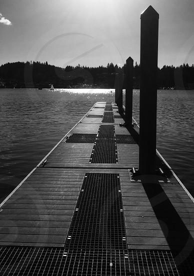 Gig Harbor peers pilings sailboat reflection black-and-white son glistening water Harbor photo