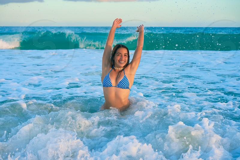 Latin beautiful bikini girl happy sitting in Caribbean beach sunset photo