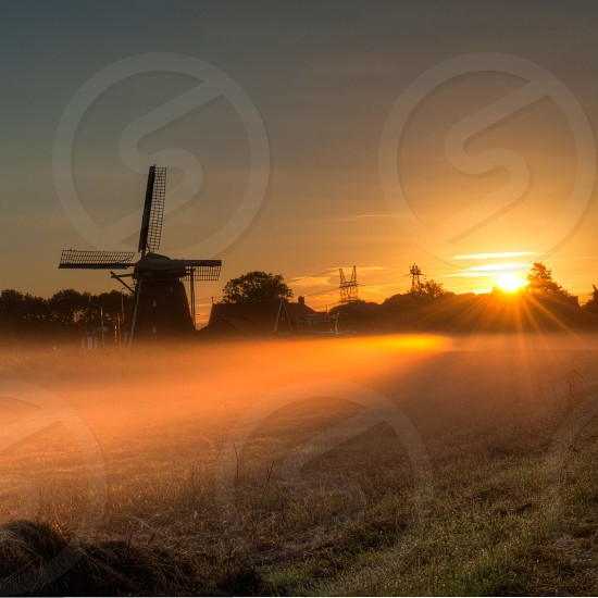 green grass field with view of windmill and trees at distance during sunset photo