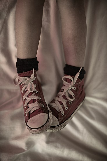 Top down shot of a teenage girls bare legs wearing red Converse shoes whilst laying on her bed photo