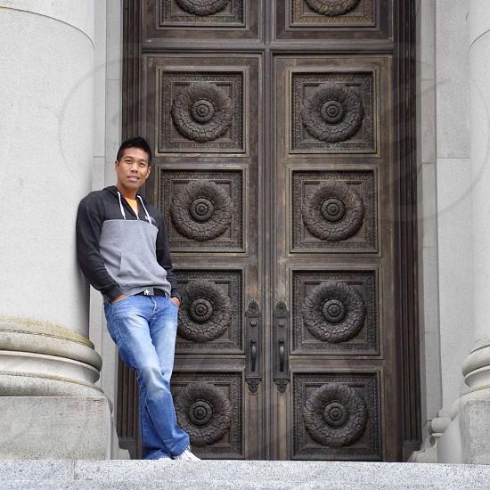 man in blue denim jeans standing leaning against grey round pillar near black wooden door photo