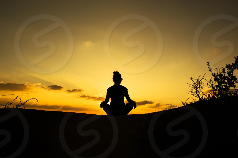 silhouette of woman meditating facing sky during golden hour photo