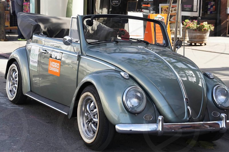 gray volkswagen convertible beetle parked on black rolled asphalt road near store photo