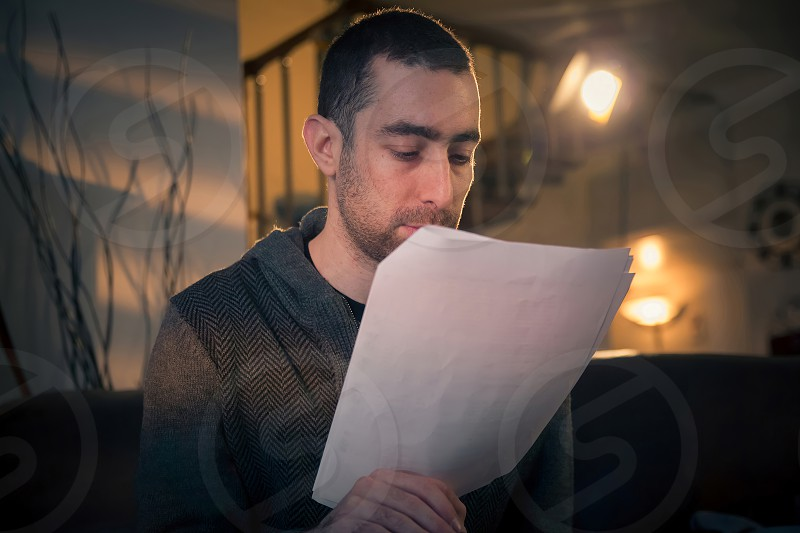 Man reading papers while sitting on a sofa in the room. photo