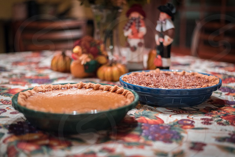 A pecan and pumpkin pie sitting on a table set with a Thanksgiving Day theme (pilgrims pumpkins and fall colored flower centerpiece). photo