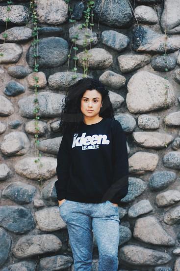 woman in black sweatshirt standing beside stone wall photo