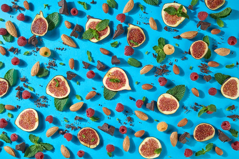 Creative sweet food composition from natural ingredients. Summer pattern with chocolate berries almond figs mint - ingredients for energy snack on a blue background. Top view. photo