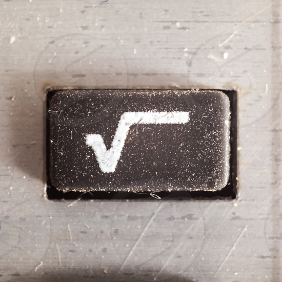 Old dirty and dusty rubberized button with written math symbol on it part of an old calculator.  photo