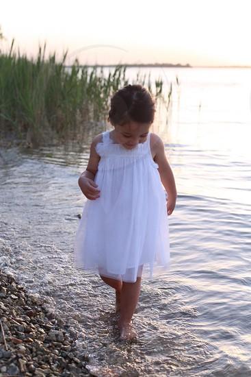 girl in white lace bodycon dress walking on seashore fashion photography photo
