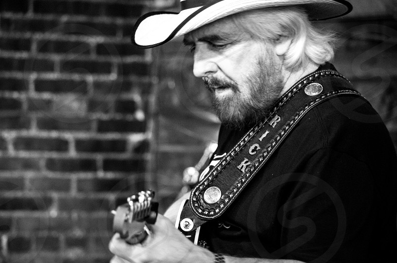 grayscale photography of man wearing cowboy hat playing guitar near brick wall photo