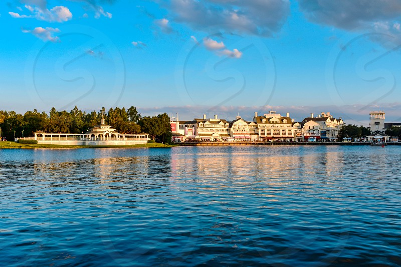 Orlando Florida. February 09 2019 . Panoramic view of lovely Victorian ride on dockside and restaurants on lightblue cloudy background at Lake Buena Vista area. photo