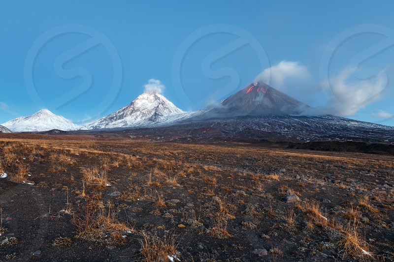 Volcanic landscape of Kamchatka Peninsula: view of eruption Klyuchevskoy Volcano lava flows on slope of volcano; plume of gas steam ash from crater. Russian Far East Klyuchevskaya Group of Volcanoes. photo