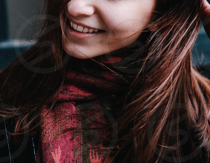 smiling brunette woman wearing a red woven scarf and black jacket photo