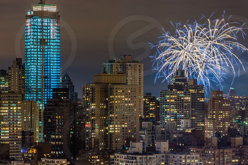 concrete raised building with blue and white fireworks during nighttime photo