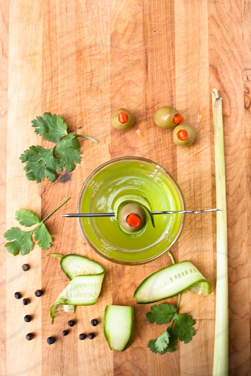 gin cocktail with cucumber and olives coriander lemon grass and juniper berries photo