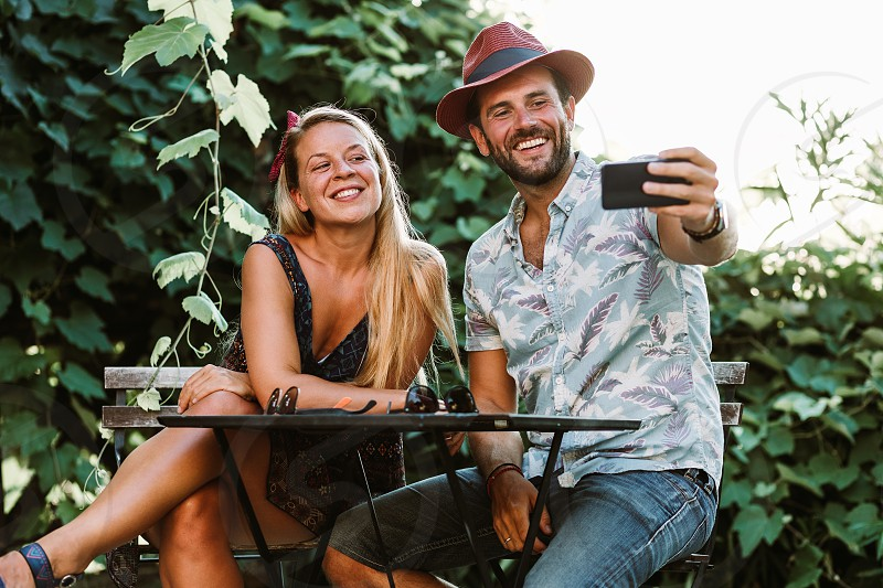Couple taking a selfie on a terrace in sunset photo
