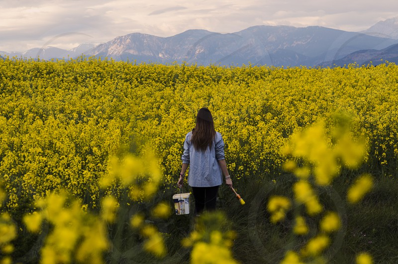 woman holding white bucket wearing grey long-sleeved shirt on yellow rapeseed flower field near mountain under white clouds blue skies daytime photo