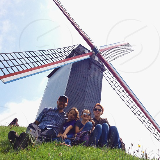 people seated on grass near windmill photo