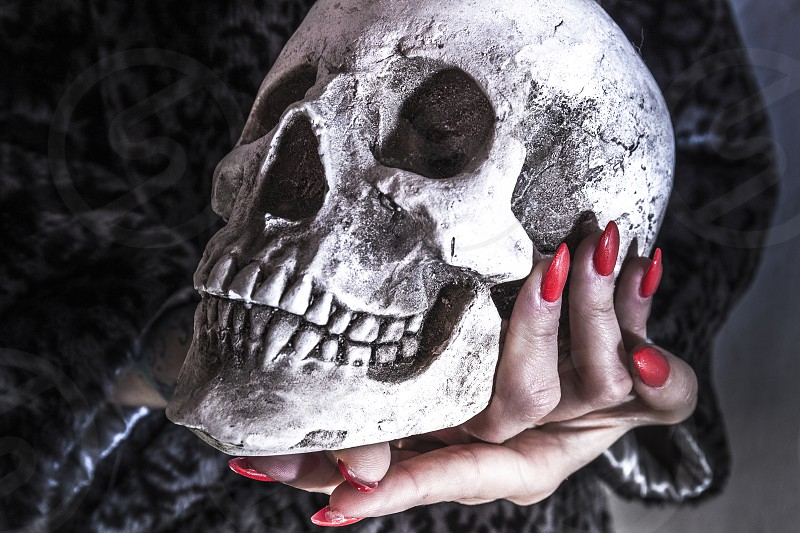 Beautiful hands with nails colored red enamel take a skull photo