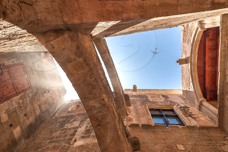 Medieval masonry building in Rhodes Downtown with framed view at above flying airplane. photo