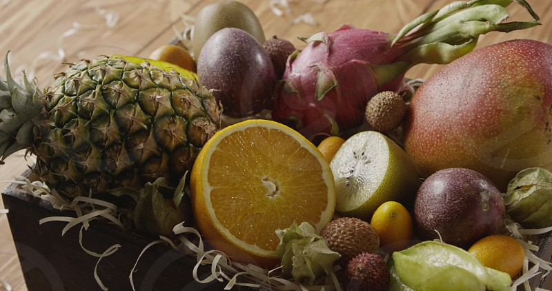 Watering of fresh organic tropical fruits in a box- ananas mango passion orange on a wooden background. Panoramic motion 4K UHD video 3840 2160p. photo