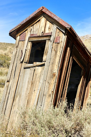 old 1800s Bodie Mono County America weathered wood dusty dry arid secluded remote ghostly Sierra Nevada Desert ghost town house settlers deserted tourism homestead American mining town gold rush historic history heritage tourist gold mining wood houses preserved desert town wild West Western tourist attraction weathered wood place poi point of interest geography eerie deserted pioneersgold seekers fortune seekers outhouse photo