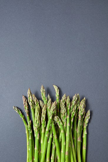 Fresh raw asparagus for cooking vegetarian food on a gray background with copy space. Top view. Vegan healthy nutrition concept. photo