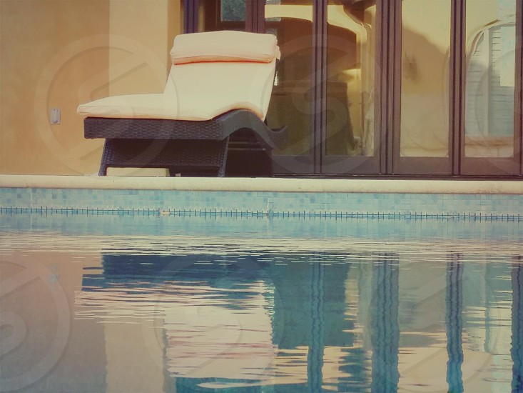 white chaise lounge beside pool during daytime photo