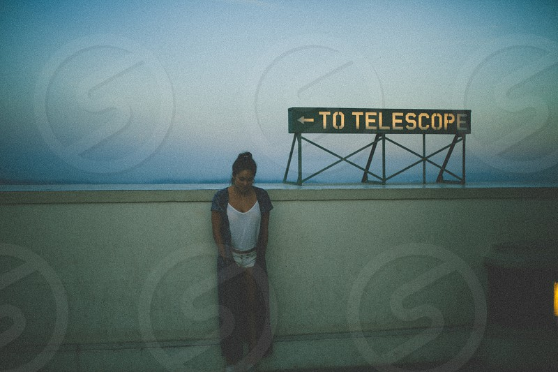 woman in black cardigan standing near to telescope sign on balcony under blue sky photo