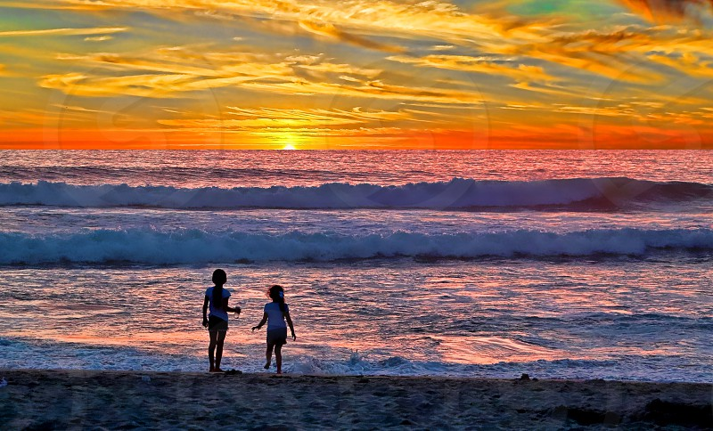 Young girls at sunset on a California beach photo