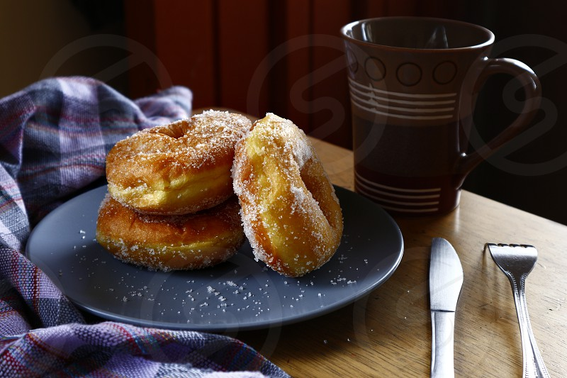 Photo of sugar raised or sugar flavored donuts on a plate and a coffee mug. photo
