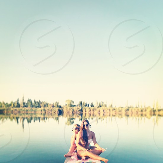 woman with black long hair in bikini sitting on dock with girl with brown short hair during day photo