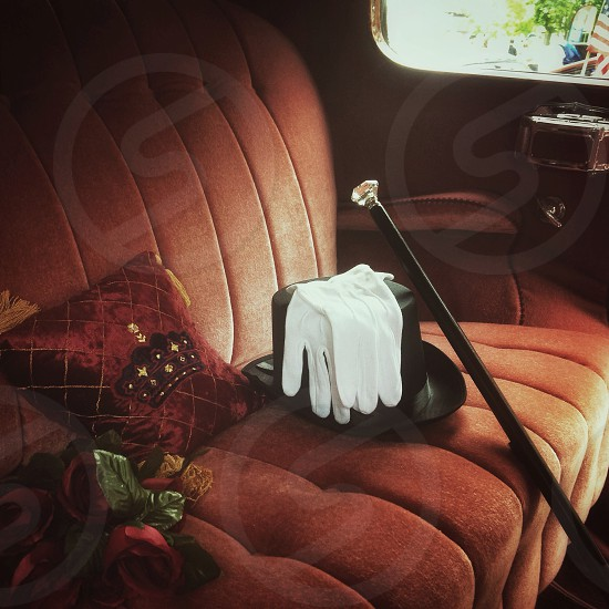 Top hat and cane - elegance of a former time  - adorn the velvet upholstery of a vintage automobile. photo