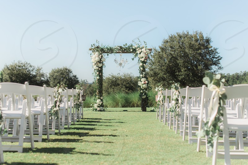 Outdoor wedding ceremony with white chairs photo