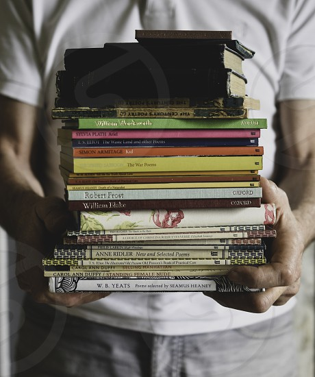 Man holding a collection of Vintage books photo