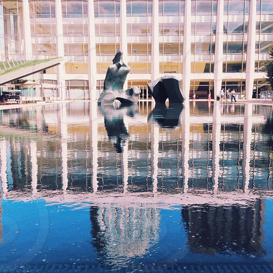 grey concrete sculpture in shallow body of water by white and clear building photo