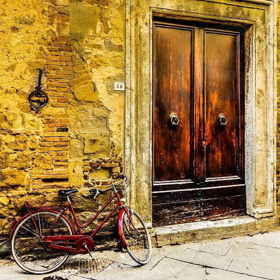 Red bicycle leaning against a wall in Pienza photo
