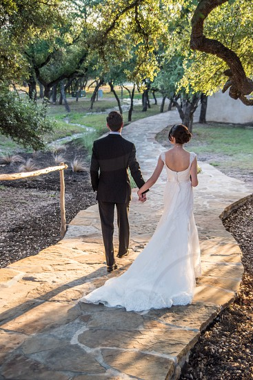 romantic couple wedding just married soulmates walking into the sunset stone path holding hands photo