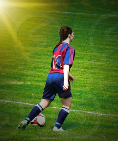 soccer female looking away hind view  play team player landscape room for words game  grass red navy photo