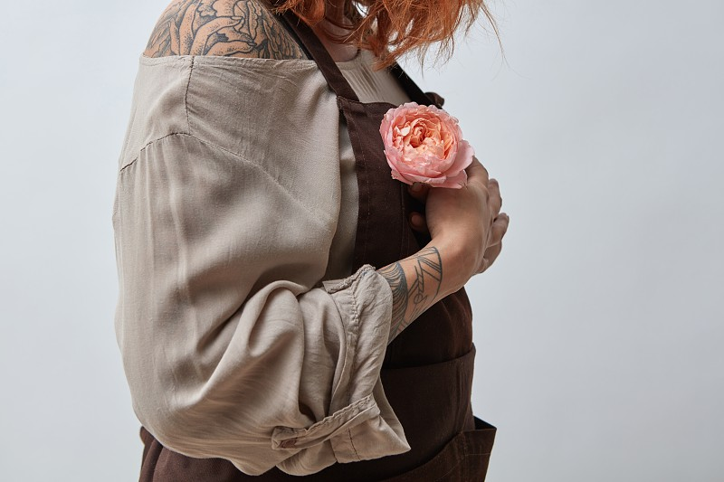 A girl with a tattoo and in an apron holds in her hand a pink flower Ranunculus on a gray background. Mother's Day Valentine's Day photo