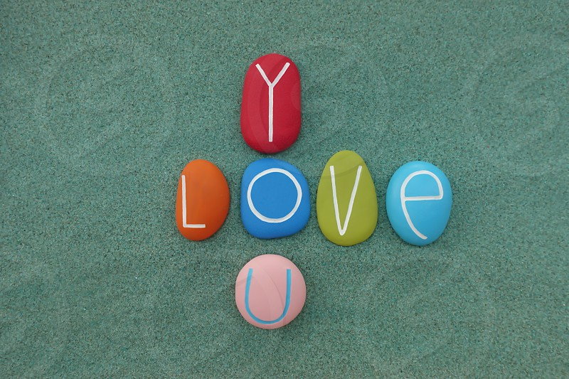 Love you with a game of colored stone letters over green sand                          photo